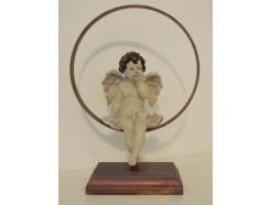 P1035736 Poly. Zittende engel in cirkel op houten voet. H x B : 29 x 21 cm.