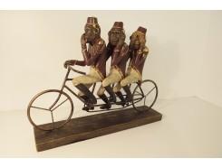 P1035702 Poly. Horen-zien-zwijgen apen op fiets met hoedjes. Hoogte x breedte : 30 x 40 cm. Goud-bruin.